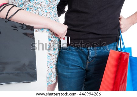 Young woman putting credit card in boyfriend pocket after doing shopping isolated on white background - stock photo