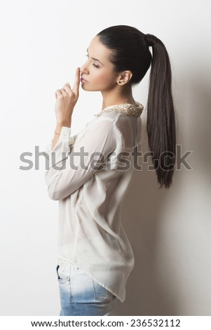 Young woman putting her finger to her lips for shh gesture  - stock photo