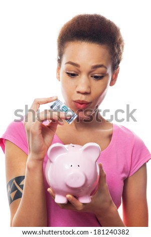 Young woman putting money in piggy bank