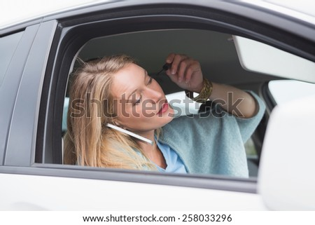 Young woman putting on makeup while calling in her car