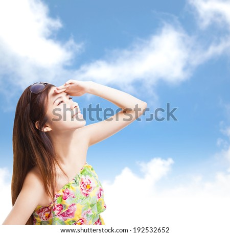 young woman raising hand to cover sunlight with blue sky - stock photo