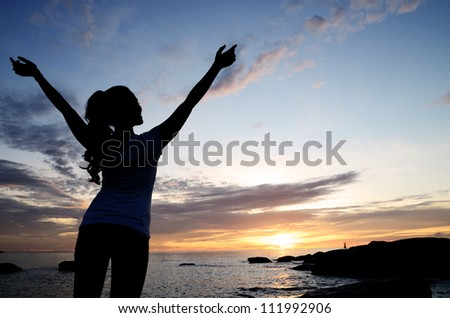 Young woman raising her hands while standing on the beach in the sunrise. - stock photo
