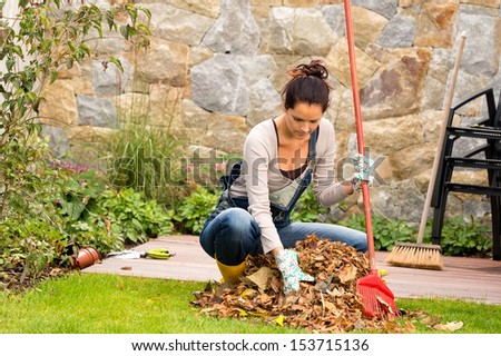 Young woman raking leaves autumn pile garden veranda housework sweeping - stock photo