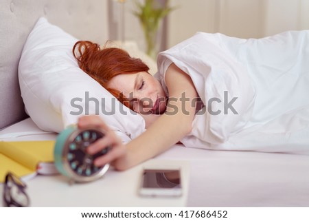 Young woman reaching out for her alarm clock to switch it off as it wakens her in the morning from a restful sleep