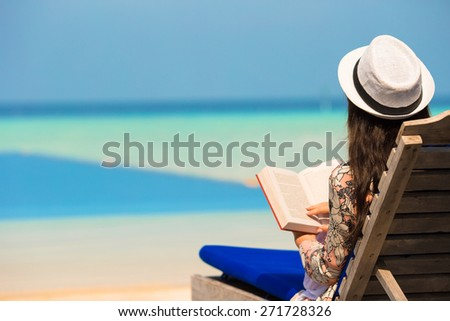 Young woman read book near swimming pool - stock photo
