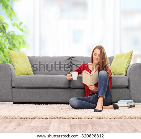Young woman reading a book and drinking coffee seated on the floor in front of a gray sofa at home shot with tilt and shift lens - stock photo