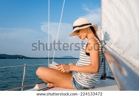 Young woman reading a book in a luxury boat. - stock photo