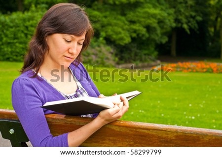 young woman reading a book  in a park - stock photo