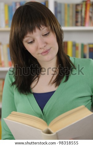 Young woman reading a book in library or bookstore
