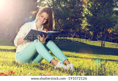 Young woman reading a book in the park with flowers  - stock photo