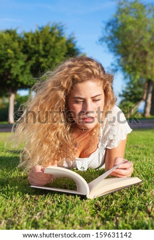 young woman reading a book lying at park on sunny day