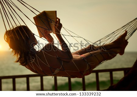 Young woman reading a book lying in a hammock on tropical resort - stock photo