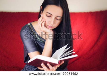 Young woman reading a book  on a sofa - stock photo