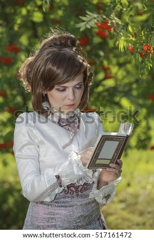 Young woman reading a book on the nature surrounded by mountain ash.