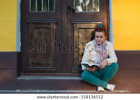 Young woman reading a book outdoor - stock photo