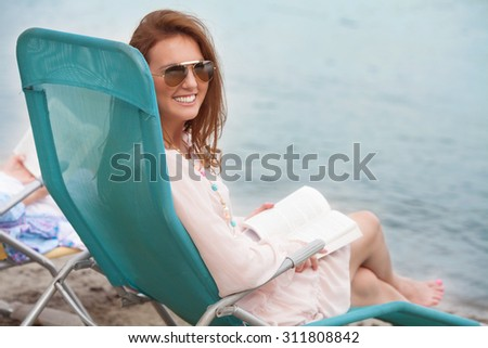 Young woman reading a book while sitting on the beach chair near the water - stock photo