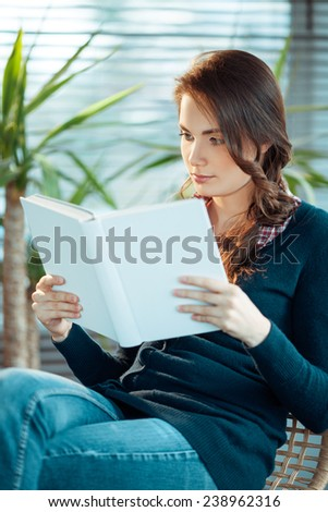 Young woman reading a book with a blank cover - stock photo