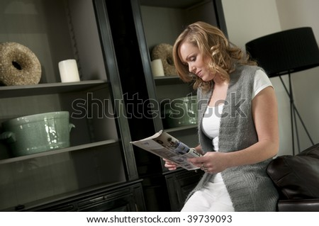 Young woman reading a magazine in a living room