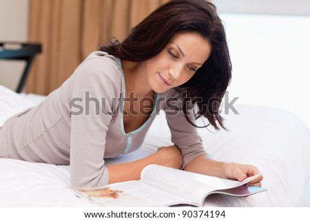 Young woman reading a magazine on the bed - stock photo