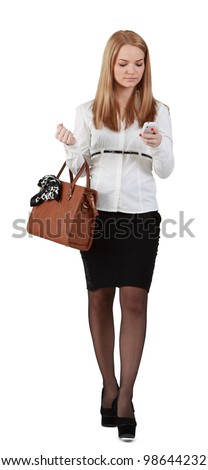 Young woman reading a phone message while walking against a white background. - stock photo