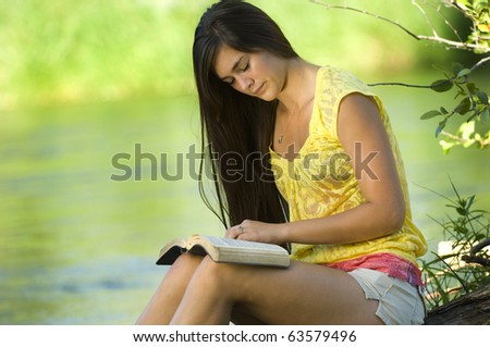Young woman reading bible by river in summer
