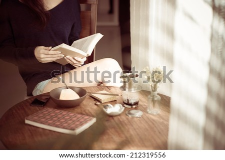 Young woman reading book at home, selective focus