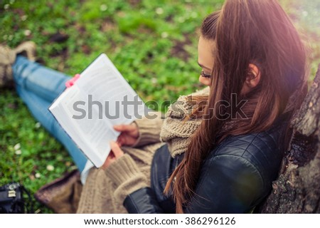 Young woman reading book. Closeup of a beautiful young woman reading book at park - stock photo