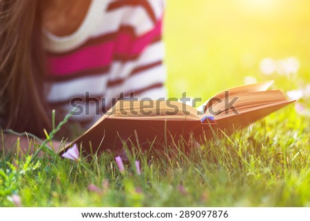 Young woman reading book in city park at summer day - stock photo