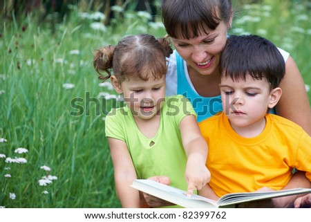 Young woman reading book little girl and cute boy in a meadow - stock photo