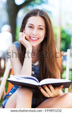 Young woman reading book outdoors - stock photo