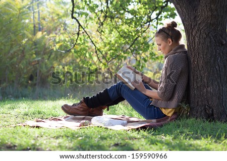 Young woman reading book under the tree during picnic in evening sunlight - stock photo