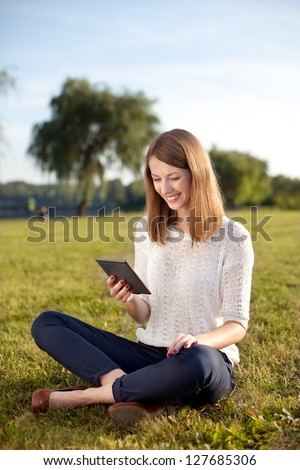 Young woman reading e-book outdoor sitting on grass