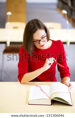 Young woman reading funny part of boring text - stock photo