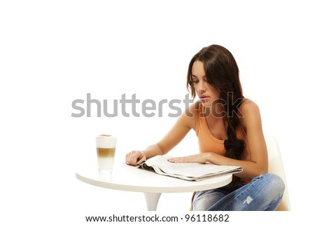 young woman reading newspaper at a table with latte macchiato coffee on white background - stock photo