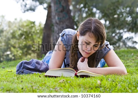 Young woman reading over the grass. - stock photo