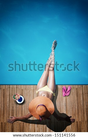 Young woman reaxing on the deck by the swimming pool at exotic resort - stock photo