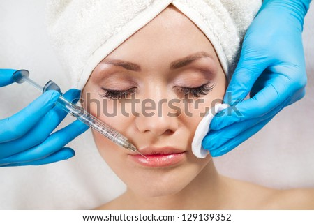 Young woman receiving a botox injection in her lips, close up - stock photo