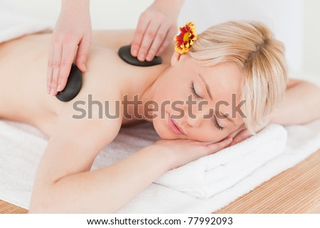 Young woman receiving a massage with hot stones in a Spa center