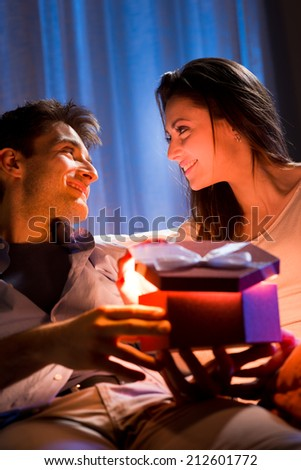 Young woman receiving a surprise gift box from her boyfriend at home. - stock photo