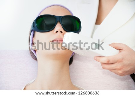 Young woman receiving electrolysis treatment on her upper lip - stock photo