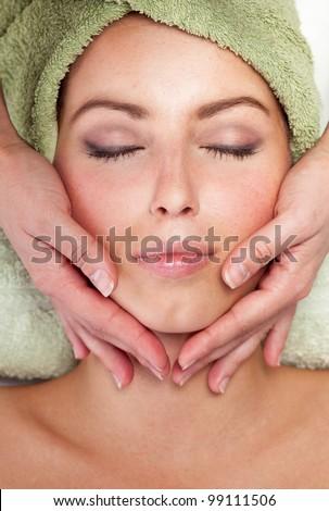 Young woman receiving facial massage - stock photo