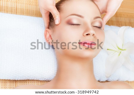 Young woman receiving facial massage with closed eyes in a spa salon