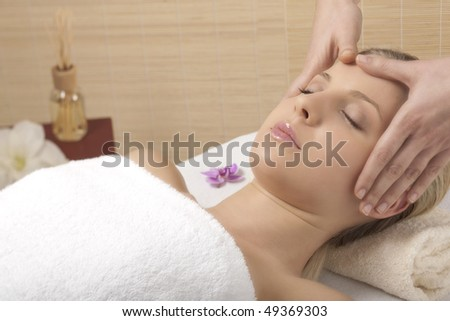 Young woman receiving head massage - stock photo