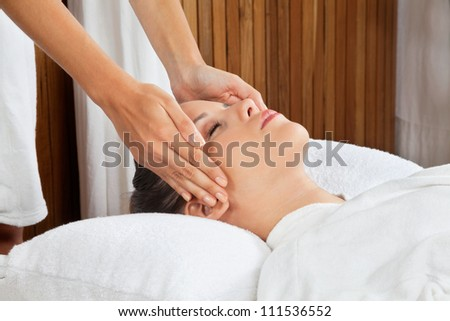 Young woman receiving head massage by masseur at health spa
