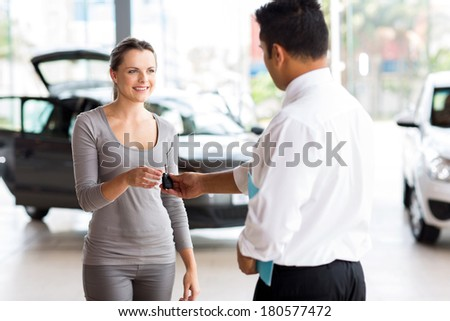 young woman receiving her new car key from salesman - stock photo
