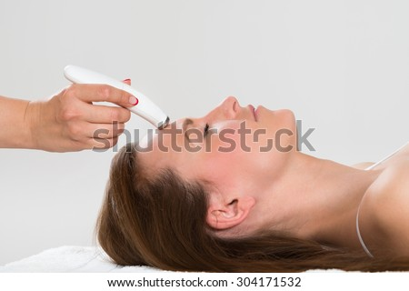 Young Woman Receiving Microdermabrasion Therapy In Beauty Clinic - stock photo