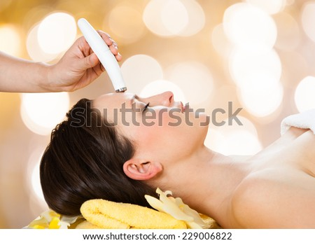 Young woman receiving microdermabrasion therapy on forehead at beauty spa - stock photo