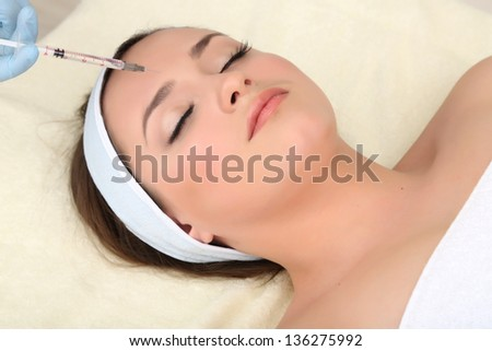 Young woman receiving plastic surgery injection on her face close up - stock photo