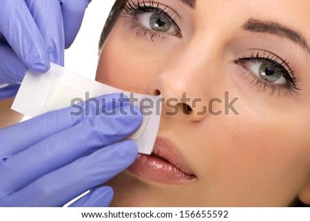 young woman reciving facial epilation - stock photo