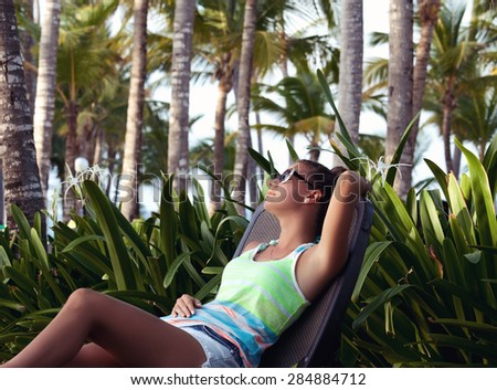 Young woman reclining on a deck chair with her hand behind her head. Girl at travel spa resort, Dominican Republic - stock photo